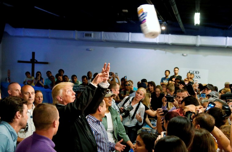 Image: President Trump throws a roll of paper towels to residents gathered in a chapel while visiting areas damaged by Hurricane Maria in San Juan, Puerto Rico