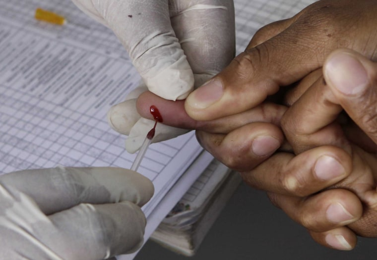 Image: A patient undergoes a pin prick blood test inside a mobile healthcare clinic