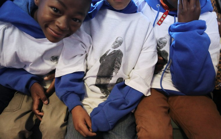 Image: Children wear t-shirts featuring a child who died of AIDS