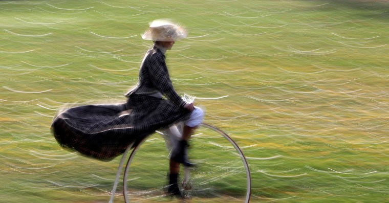 Image: A participant wearing historical costume rides her high-wheel bicycle before the annual penny farthing race in Prague