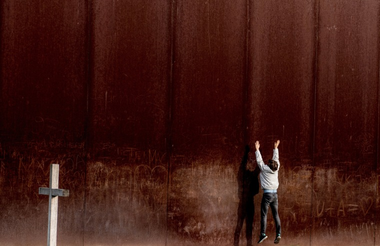 Image: A man jumps in front of a metal wall, part of the Berlin Wall memorial site