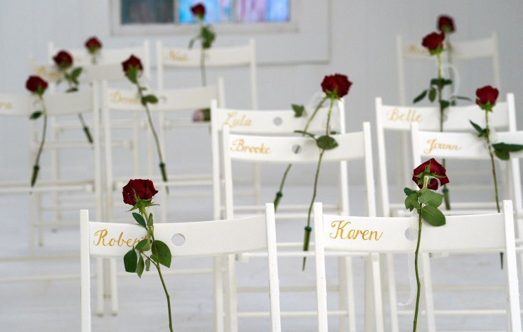 Image: Roses are placed on chairs for the victims of last week's shooting at the First Baptist Church