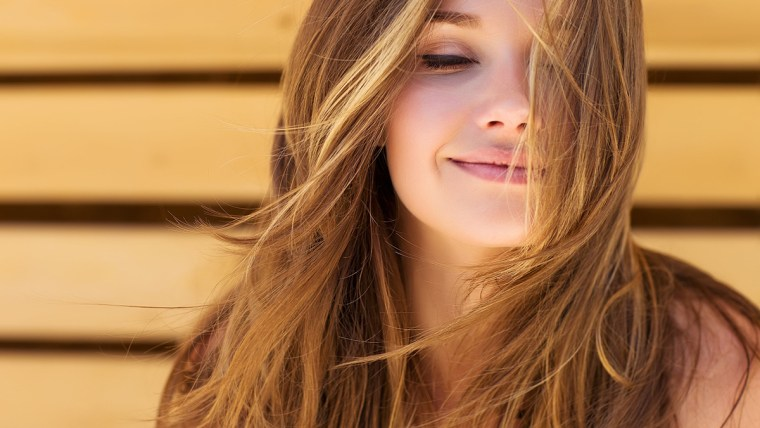 Girl smiling with hair flowing.