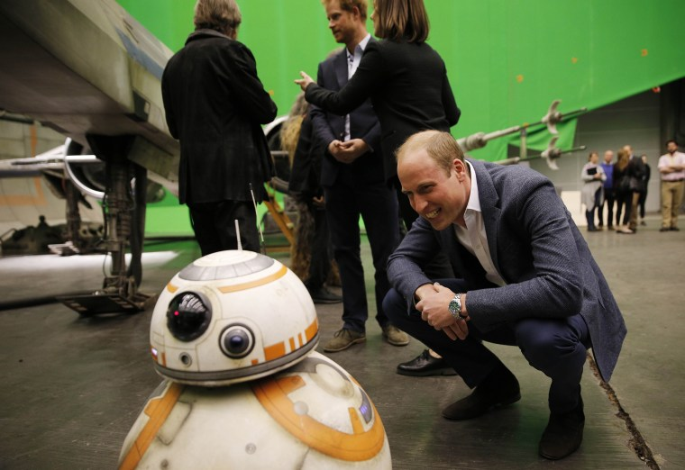 Britain's Prince William, Duke of Cambridge smiles at BB-8 droid during a tour of the Star Wars sets at Pinewood studios in Iver Heath, west of London on April 19, 2016.