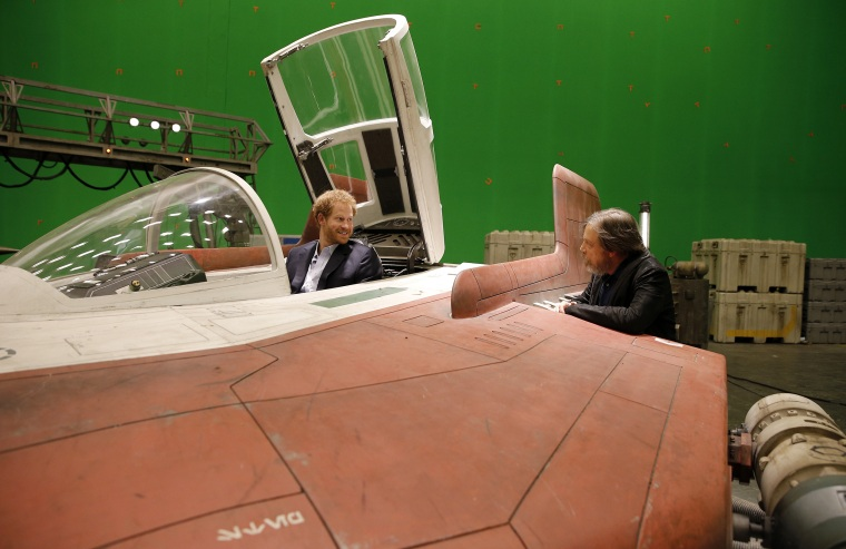 Britain's Prince Harry sits in an A-wing fighter as he talks with US actor Mark Hamill during a tour of the Star Wars sets at Pinewood studios in Iver Heath, west London, Tuesday April 19, 2016.
