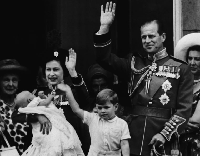 Queen Elizabeth II holds her 12 week old son, Prince Edward, as she stands with her husband Prince Phillip on the balcony of Buckingham Palace on June 13, 1964. (AP photo)