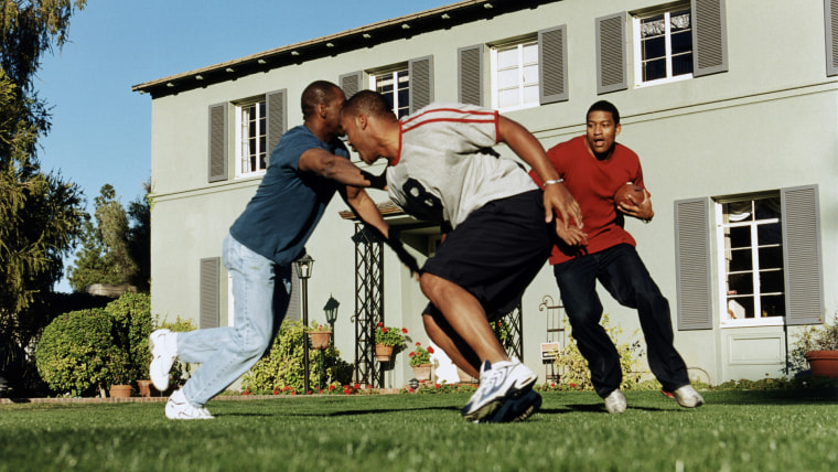 Three men playing football outside house