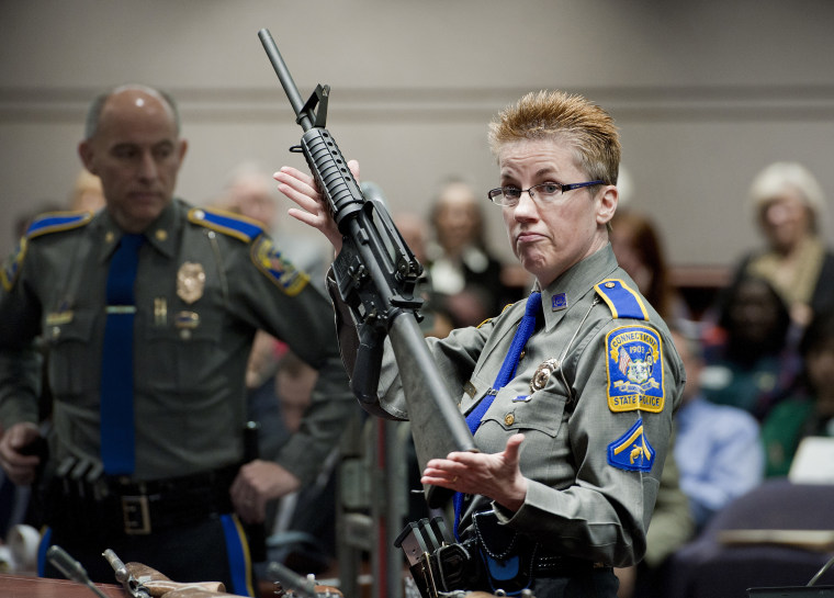 A Connecticut State Police officer holds a Bushmaster AR-15 rifle, the same make and model of the gun used by Adam Lanza, during a hearing reviewing gun laws in Hartford, Connecticut, in 2013.
