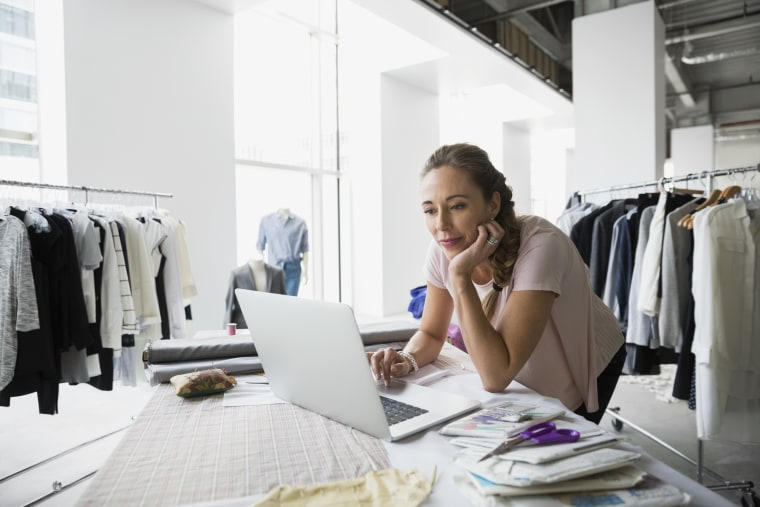 Fashion designer with sewing patterns using laptop, business woman on computer