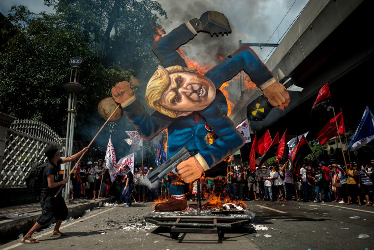 Image: Protesters burn an image of Trump fashioned on a swastika as they march the streets of Manila during the start of the ASEAN meetings between heads of state on Nov. 13.