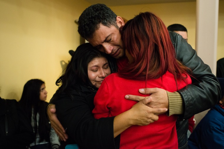 Image: A family from Washington hugs after finding out they are safe as immigrants gather to watch an announcement on immigration