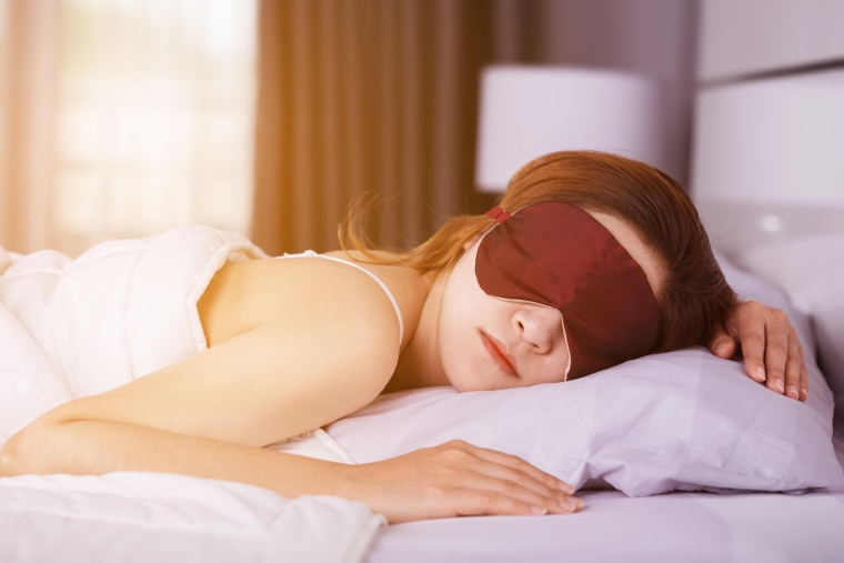 Image: A woman sleeps with eye mask