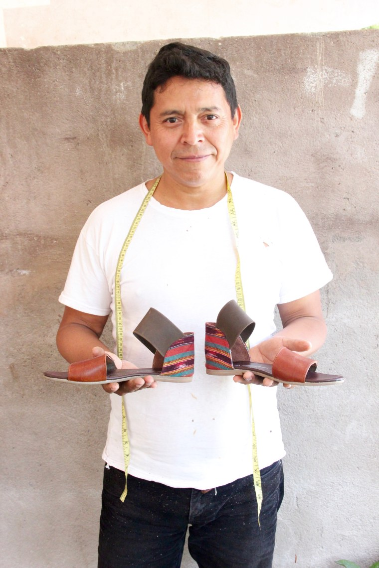 One of Teysha's artisan artists displays a Lonel and Siempre sandal.