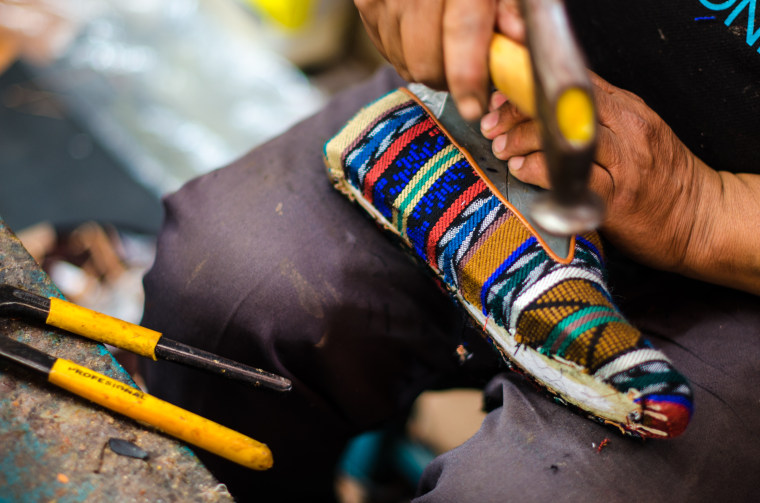 An artisan puts the final touches on a shoe.