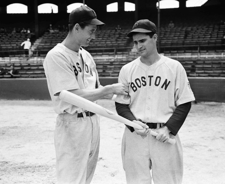 Boston Red Sox outfielder Ted Williams, left, tests the arm of Red Sox second baseman Bobby Doerr in 1942.
