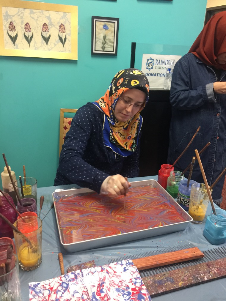 A woman uses water marbling techniques to create a piece of art at the Turkish Festival in Broken Arrow, Oklahoma.