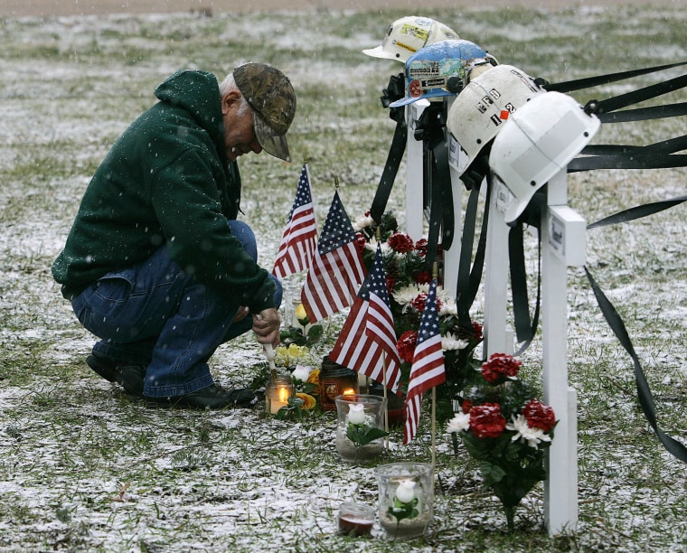 Image: A man lights candles at the base of crosses for four miners killed in the Sago Mine explosion in 2006