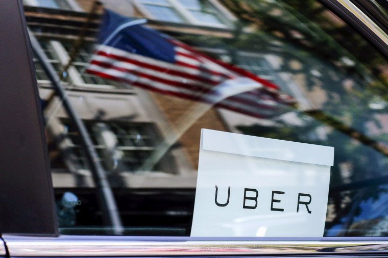 Image: An Uber sign is seen in a car in New York