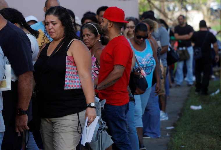 Image: Residents affected by Hurricane Maria wait in line to receive unemployment checks outside a government unemployment office along Puerto Rico Highway 2, outside San Juan