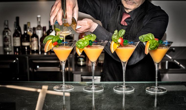 Image: A bartender pours cocktails