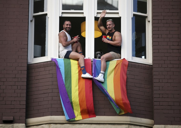 Image: Two men watch a parade from a window as members of the gay community and their supporters celebrate