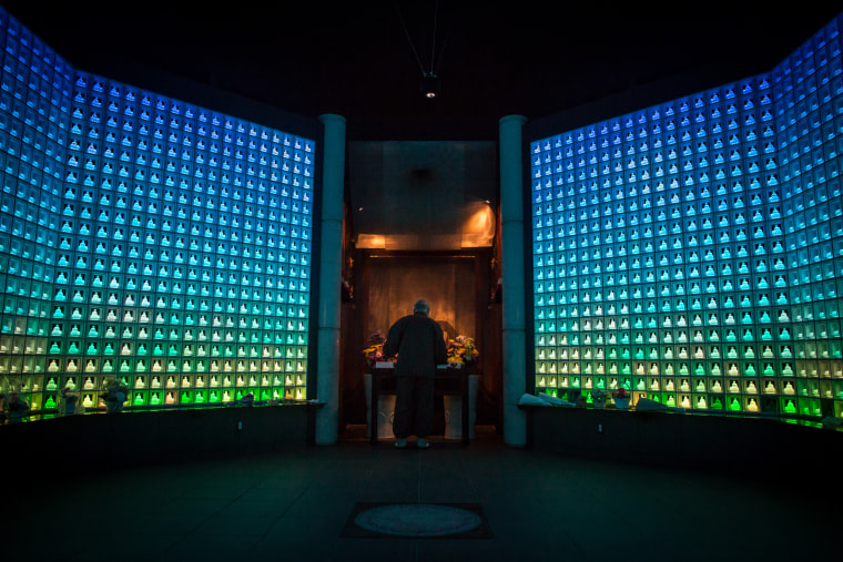 Image: Koukokuji temple head priest Yajima Taijun demonstrates a prayer ritual inside the Ruriden columbarium