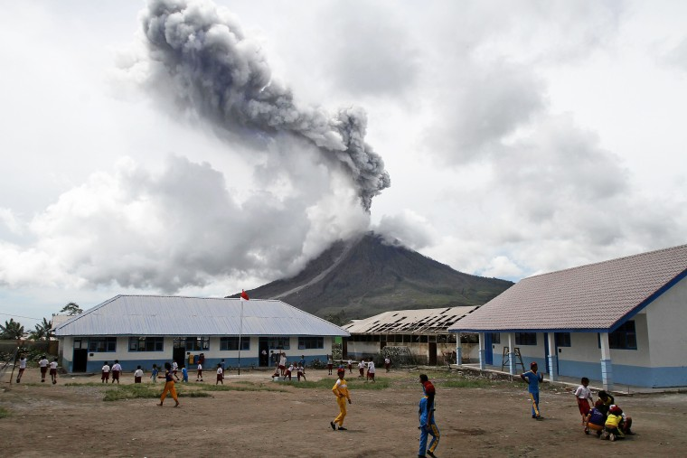 Image: Primary school children play outside their classroom as Mount Sinabung, active since 2010, erupts in the distance in Naman Teran Village, Karo