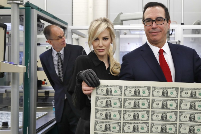Image: Mnuchin and his wife Louise Linton hold up a sheet of new $1 bills