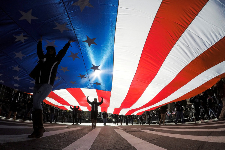 Image: People carry the U.S. flag during the Veterans Day Parade in New York