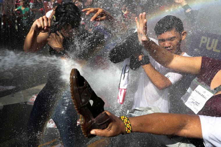 Image: Protesters are hit by a water cannon as they try to march towards the U.S. embassy during a rally against U.S. President Donald Trump's visit, in Manila
