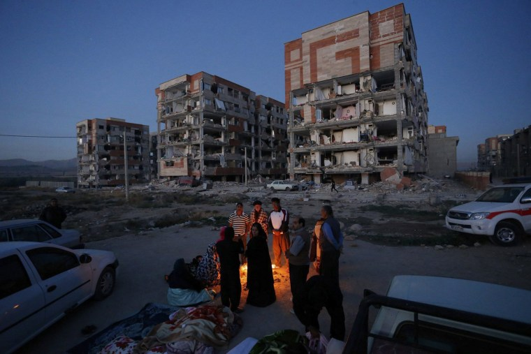 Image: Iranian victims of an earthquake gather outdoors near a fire