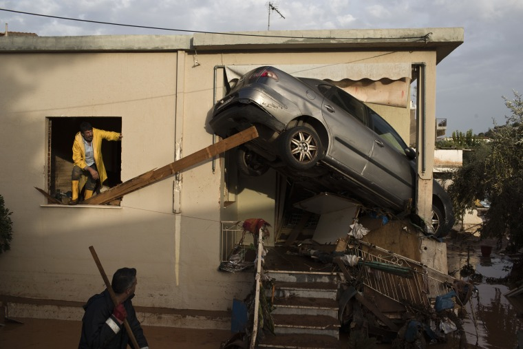 Image: Workers try to remove a flipped over car at the entrance of a house in the town of Mandra
