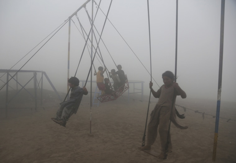 Image: Children ride swings in a playground surrounded by smog in Lahore