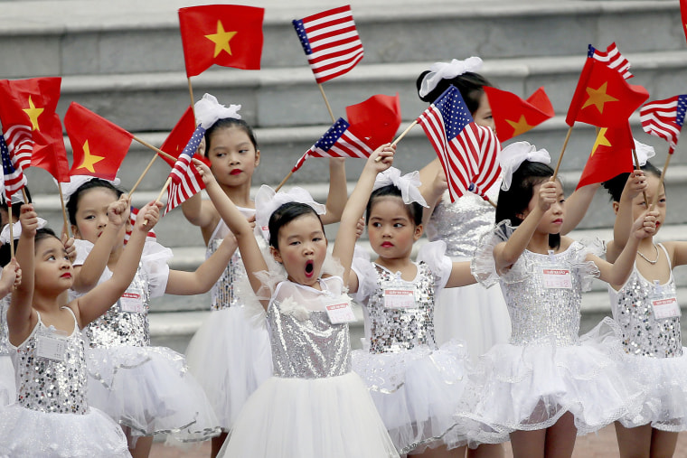 Image: Vietnamese children wave flags before a welcome ceremony of U.S. President Donald Trump