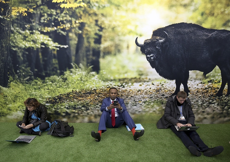 Image: Participants sit on the floor in front of a poster during a break at the UN Climate Conference