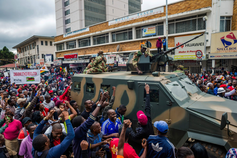 Image: People cheer a passing Zimbabwe military vehicle