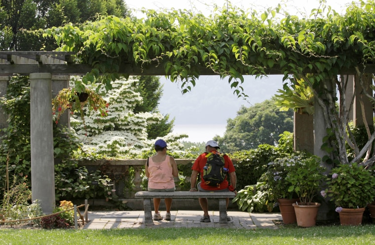 Image: Tourists rest on a bench overlooking the Hudson river and gardens at Wave Hill, a public garden and cultural center in the northwest Bronx in New York, on June 10, 2008.