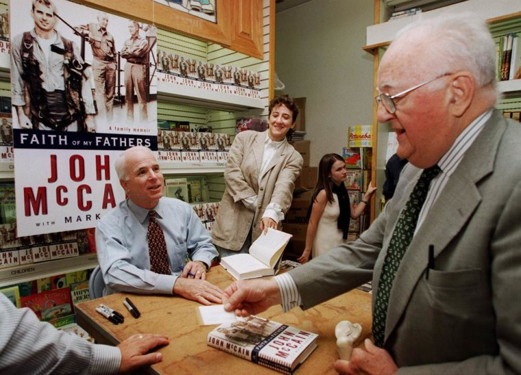 "Image: McCain signs copies of his book ""Faith of My Fathers"""