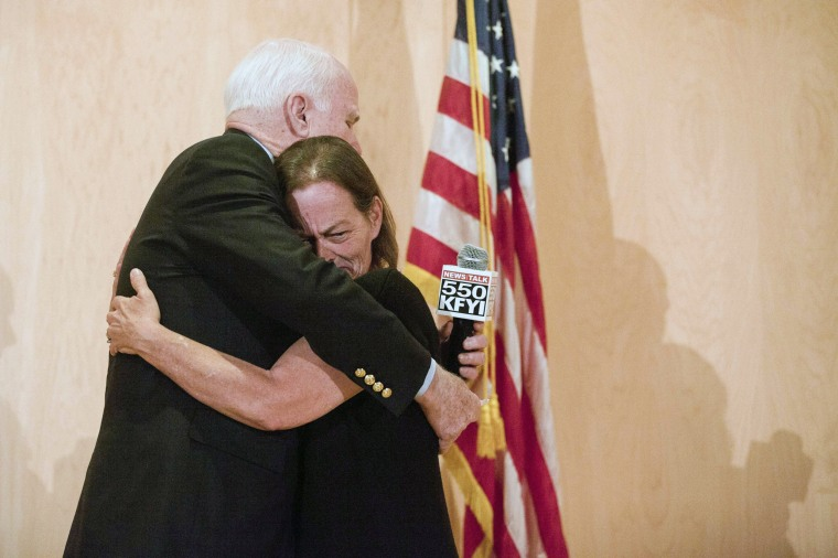 Image: Senator John McCain hugs the wife of a dead veteran at a community forum over recent allegations of gross mismanagement and neglect of veterans health care in Phoenix
