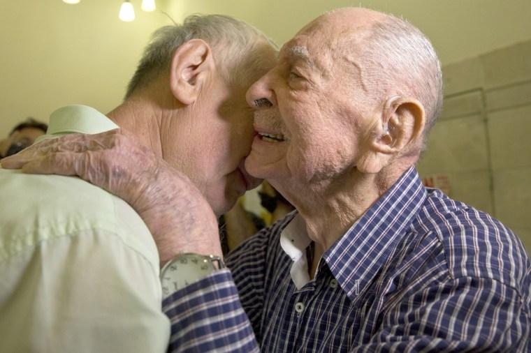 Image: Israeli Holocaust survivor Eliahu Pietruszka, right, embraces Alexandre Pietruszka as they meet for the first time in Kfar Saba on Nov. 16, 2017.