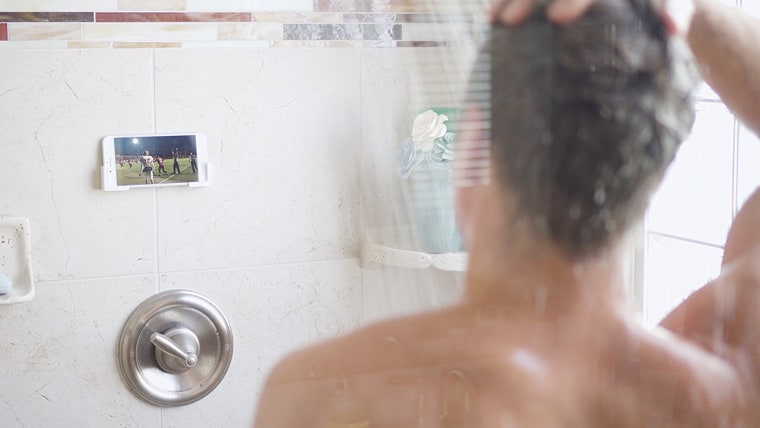 Man in shower watching football