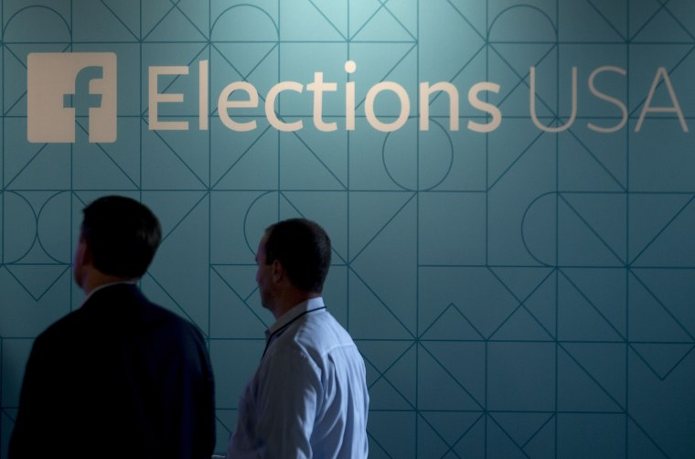 Image: Two men stand under a Facebook Elections USA sign at the first GOP primary debate