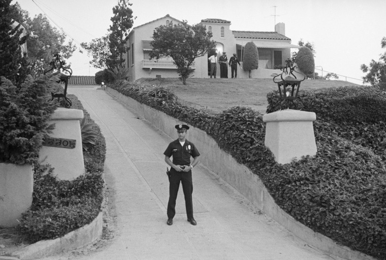 Image: A police officer blocks the driveway while other officers search in front of the house where Leon La Bianca, 44, and his wife Rosemary, 38, were stabbed to death in Los Angeles on Aug. 10.