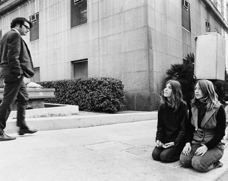 Image: Two members of the Manson Family known as Kitty Lutesinger, left, and Kathy Gillies, kneel on the sidewalk outside the Los Angeles Hall of Justice, Dec. 30, 1970, while the trial of Manson murder trials continue inside.