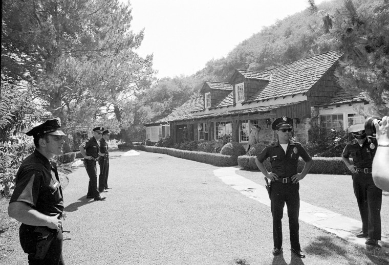 Image: Police officers stand on the Tate property, where her body and those of five others were found murdered, on Aug. 9, 1969.