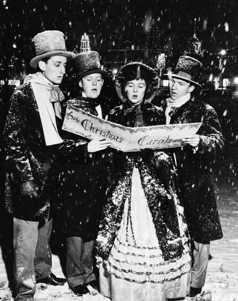 Image: Jerry Wooden, Neal Stuessi, Patricia Kidd, and Bill Piehler, dressed in 1860s style outfits sing Christmas songs