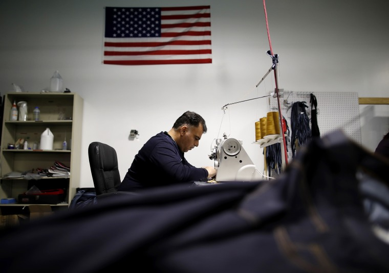 Image: An employee operates a sewing machine to stitch a pair of jeans at the Dearborn Denim facility in Chicago