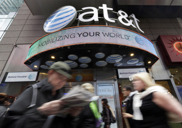 Image: People pass an AT&T store in New York's Times Square