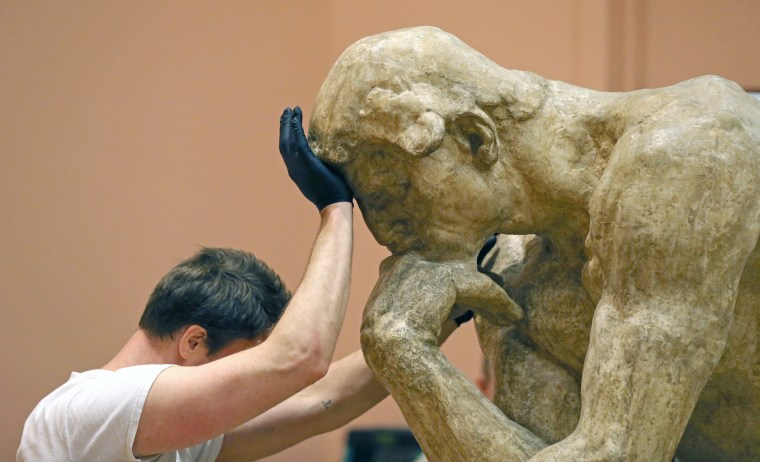 """Image: A worker moves a rare plaster cast of Rodin's """"The Thinker"""""""