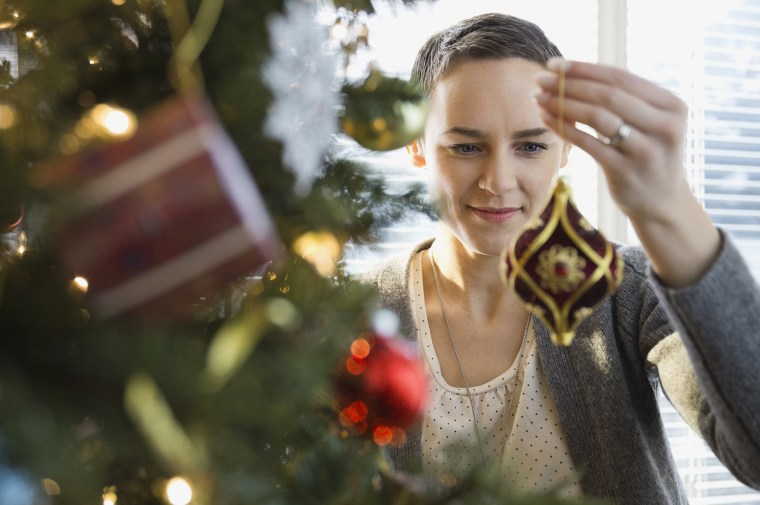 Image: A woman decorates a Christmas tree at home